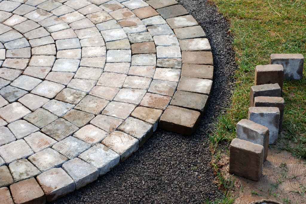 Patio bricks installation. Pavers in a circular pattern.